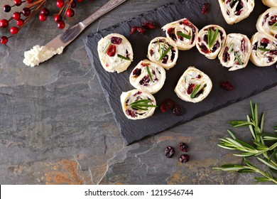 Cranberry, cream cheese pinwheel appetizers. Holiday food concept. Top view, on a dark background.