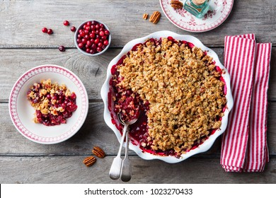Cranberry crumble, crisp in a baking dish. Wooden background. Top view.