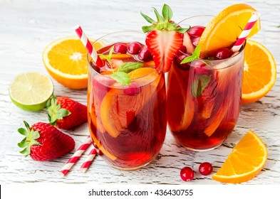 Cranberry drink, homemade lemonade or sangria with citrus fruits and berries on white background, refreshing cocktail for hot summer days