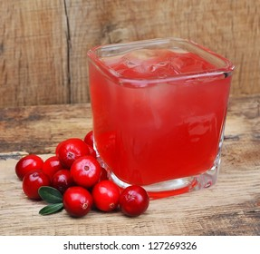 Cranberry drink on wooden table. Berry cocktail