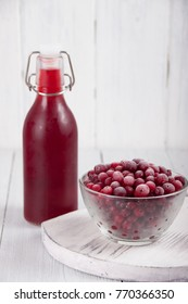 Cranberry juice in a bottle and a cranberries in a glass bowl on a white table