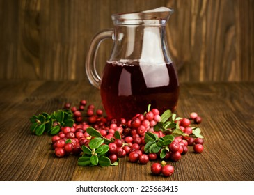 cranberry juice and cranberries on wooden background