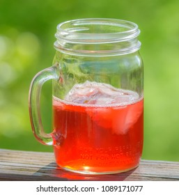 Cranberry juice in glass handle jar in sun with ice