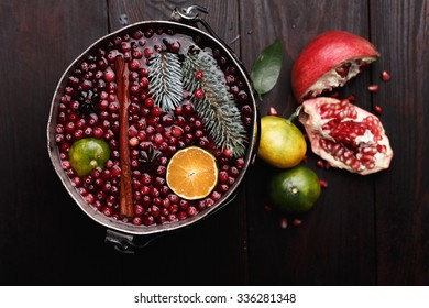 Cranberry mandarin pomegranate punch or mulled wine in a rustic aged pot over wooden backdrop