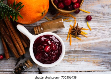 Cranberry sauce with ingredients on wooden table. Space for text