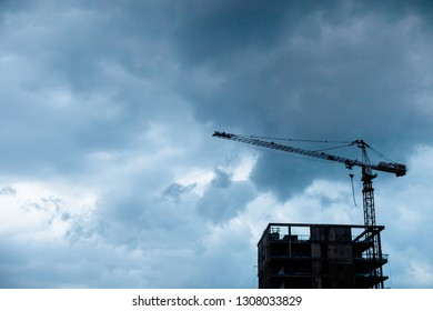 Crane above building in construction below cloudy winter sky