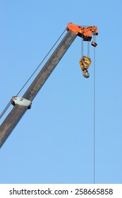 crane boom with hooks with blue sky background.