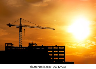 crane and building construction black silhouette on sunrise sky background