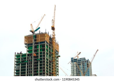 Crane and building construction site against with white isolated background. Construction site background. Hoisting cranes and new multi-storey buildings. Industrial background.