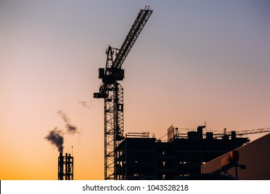 Crane and building construction site with pipe with smoke on background of sunset sky. Industrial landscape with silhouettes of cranes over evening sunlight. city Environmental problem