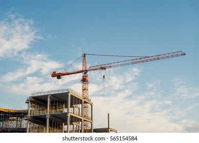 Crane and building construction site in sunrise light against blue sky and clouds
