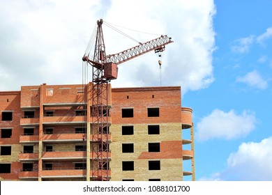 The crane is building a dwelling house. Facade of unfinished multi-storey building