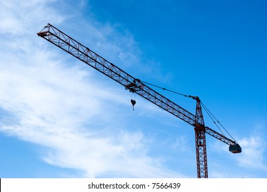 Crane for building industry on background of the blue sky with clouds