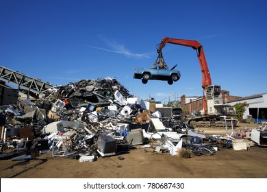 Crane with claw tossing trucks at scrapyard recycling center