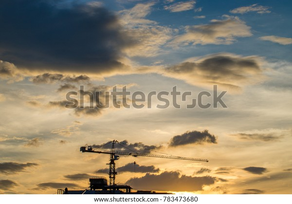 Crane at construction building and silhouettes over of blue sky.