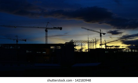 crane and construction and sunset sky ,Industrial construction cranes and building silhouettes over sun at sunrise. real estate house and condominium business investment background