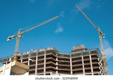 Crane developing modern residential buildings against blue sky