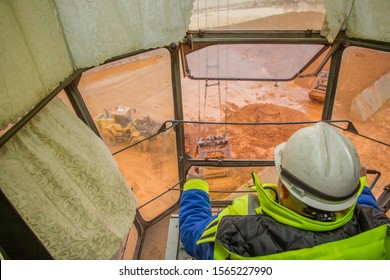 The crane driver in the cabin of the Sokol gantry crane unloads nickel ore with a grab