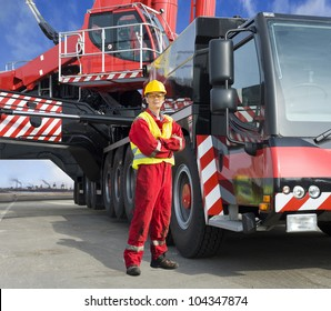 Crane driver, posing next to the huge mobile crane he's operating