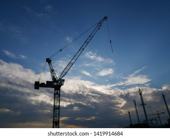 Crane Erected Behind Sunset Sky With Clowds