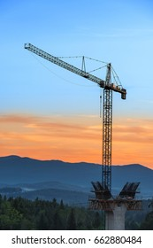 Crane in the forest on the background of mountains. Building new road in mountains.