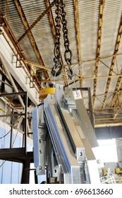 Crane hook lifts cargo on production background