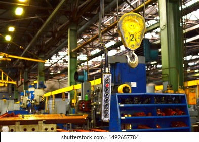 Crane hook of the overhead crane in the workshop of an industrial plant.  Push remote control switch for lifting crane in the factory