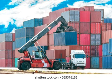 Crane lifting up container in railroad yard beautiful  blue sky background