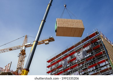Crane lifting a wooden building module to its position in the structure. Construction site of an office building in Berlin. The new structure will be built in modular timber construction.