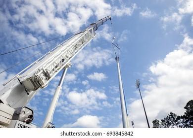 Crane lifts a light pole to its permanent position.