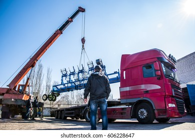 a crane lifts a metal structure on the truck
