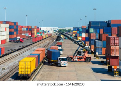crane loading container box from container truck to container train in commercial shipping port with logistics background, logistics and supply chain concept