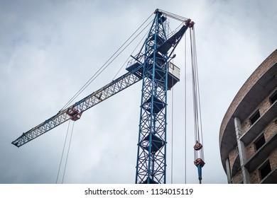Crane near the brick high-rise building under construction against the blue sky, modern construction