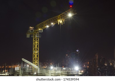 Crane on top of under construction building at night