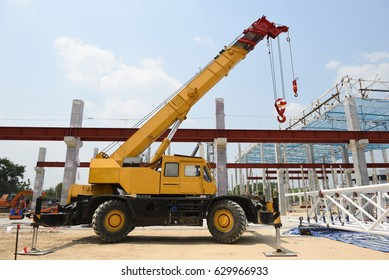Crane operator and Mobile crane machine stand by waiting for lift steel roof truss under the construction building industrial factory