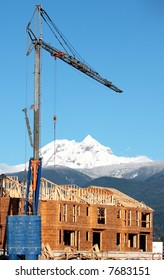 A crane seems to tower over a peak near Whistler, BC, Canada.  Development is booming in the nearby town of Squamish.