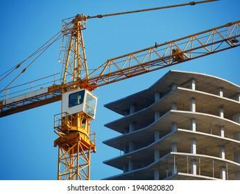 Crane. Self-erection crane over construction site. Crane near bulding. Industrial background.