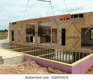Crane setting half of a pre built house onto a basement foundation