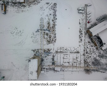 A crane at a snow-covered shipyard. Snowy day, blizzard. Aerial drone view.