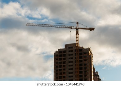 crane stands near new unfinished building on the background of evening cloudy sky with, side view. real estate investment concept