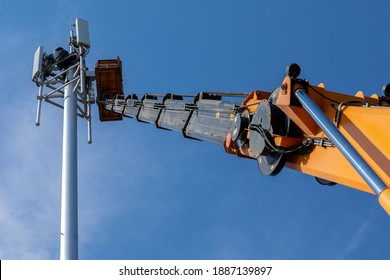 Crane with telescopic boom lift used as an aerial working platform. Worker install cellular base station with transmitters 3G, 4G and antennas on cell tower on background of blue sky. Focus on arrow.