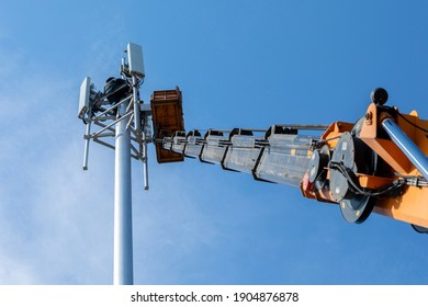 Crane with telescopic boom lift used as an aerial working platform. Worker install cellular base station with transmitters 3G, 4G, and antennas on cell tower on blue sky background. Focus on tower