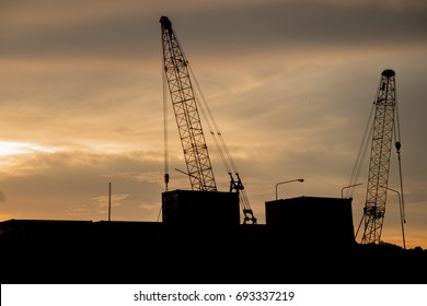 Crane transport container docks area silhouette with sunset background.
