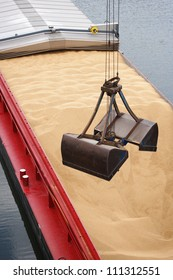 crane unloading a barge filled with sand, closeup of shovel