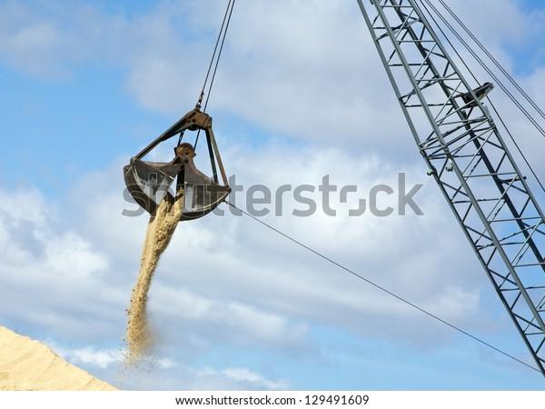 crane unloading sand with large iron dump bucket