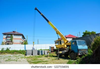 Crane unloads truck with concrete slabs on construction site of largest builder