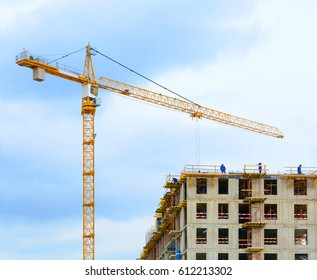 Crane and workers at construction of residental building against blue sky with clouds