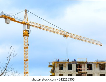 Crane and workers at construction of residental building against blue sky