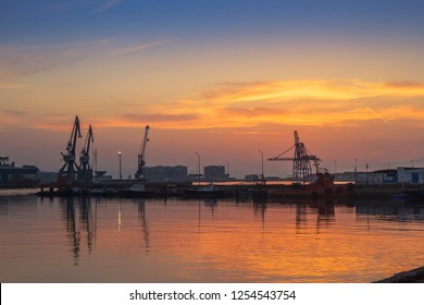 Cranes and boats on the dock of Vilagarcia de Arousa commercial harbor at golden twilight