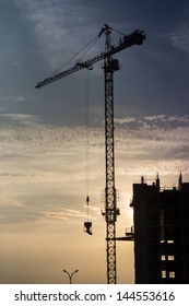Cranes and building construction site against blue sunset sky